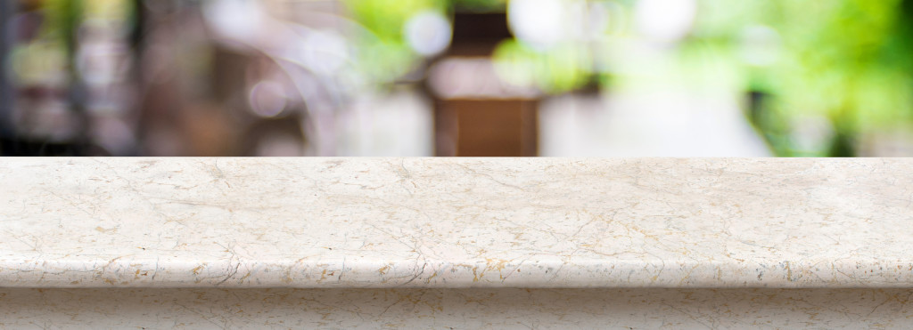 Empty luxury white marble table top with blurred cafe bokeh